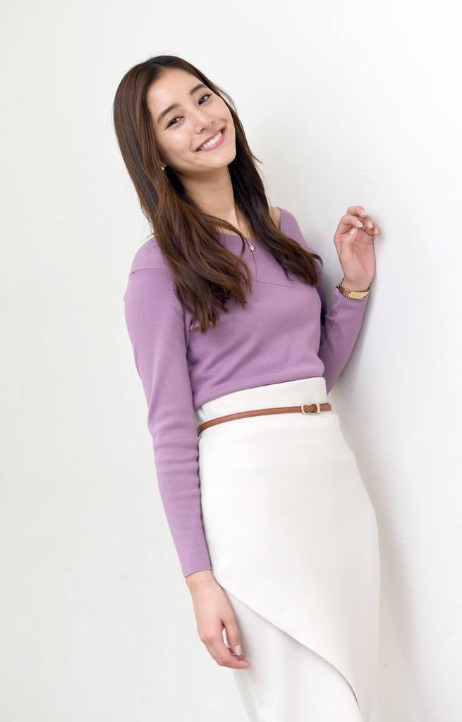 新木優子さんのファッションはトップスがラベンダー色、白のタイトスカートにキャメル色のベルトをしています